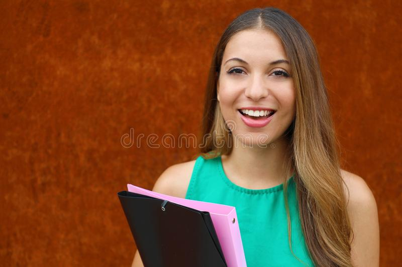 Close up young business woman holding folders outdoor on rust background with copy space.  royalty free stock photo
