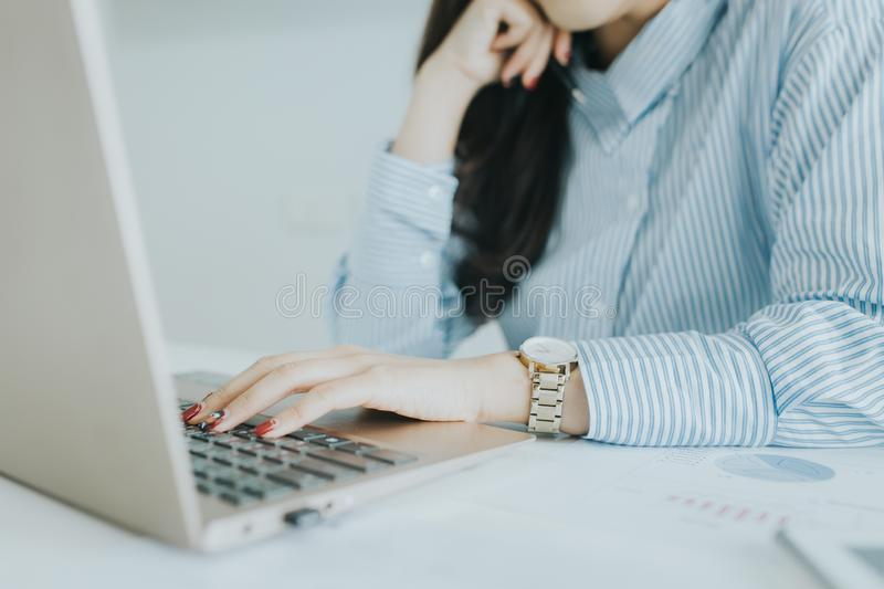 Close up of young business woman working on her laptop at desk. royalty free stock photo