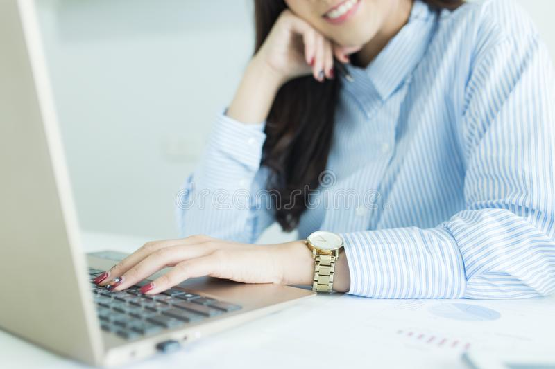 Close up of young business woman working on her laptop at desk. stock photography