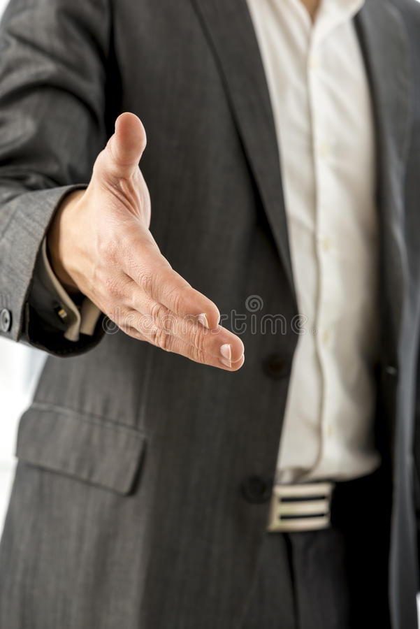 Close up Young Businessman in Black Suit Offering you a Hand in. Handshake Gesture at the Camera royalty free stock photos