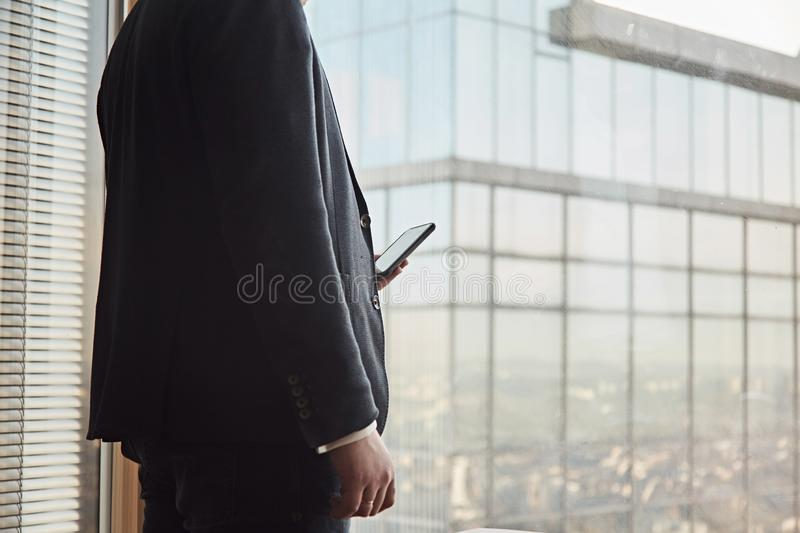 Close up of young businessman in black suit using smart phone while staying at his office. stock photography
