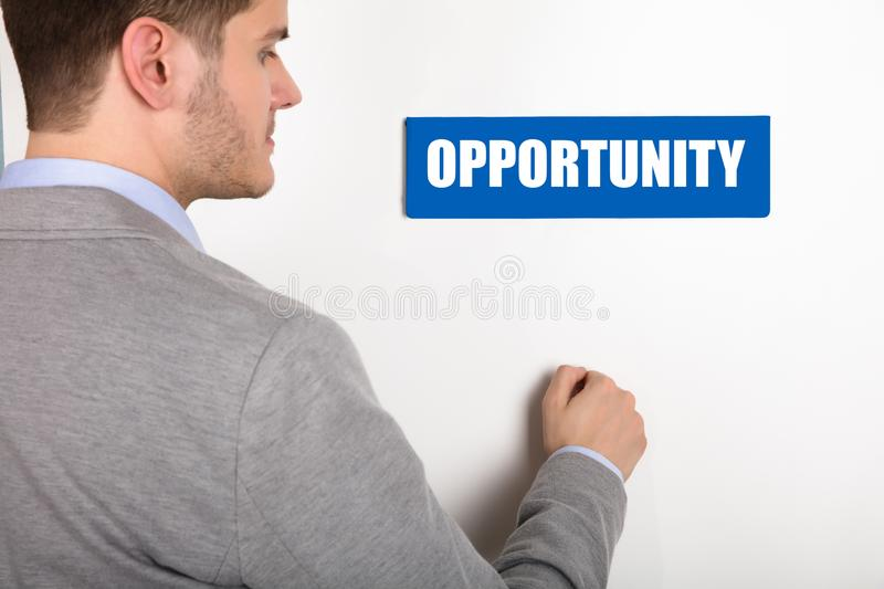 Businessman Knocking Door With Opportunity Text. Close-up Of A Young Businessman Knocking White Door With Opportunity Text stock image