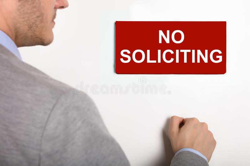 Businessman Knocking Door With No Soliciting Nameplate. Close-up Of A Young Businessman Knocking White Door With Red No Soliciting Nameplate royalty free stock images