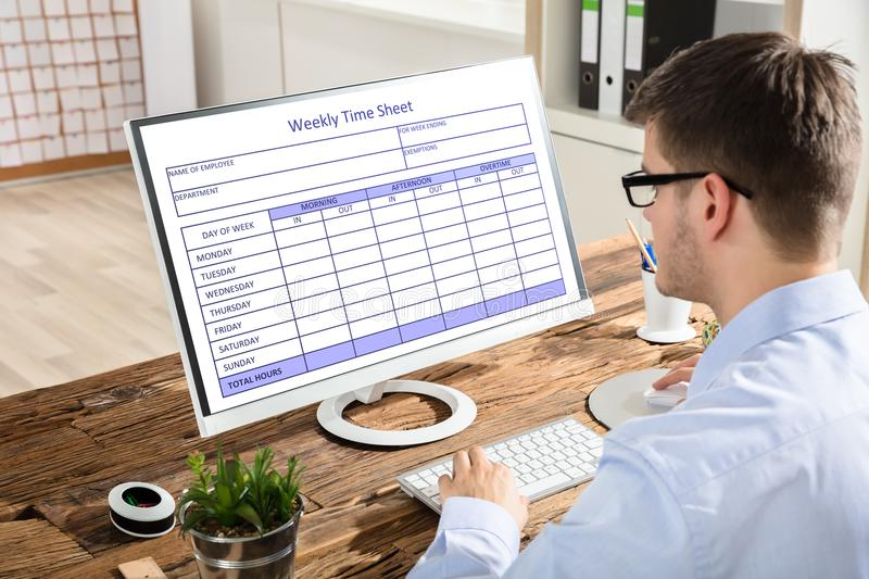 Businessman Looking At Weekly Time Sheet On Computer stock images