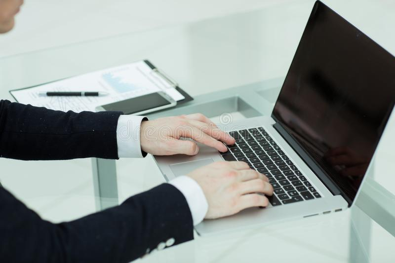 Close up. young businessman typing on laptop. royalty free stock image