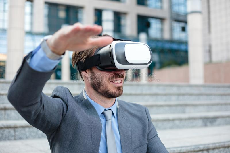 Close up of a young businessman using VR goggles in front of an office building. Selective focus concept, focus on head stock photos