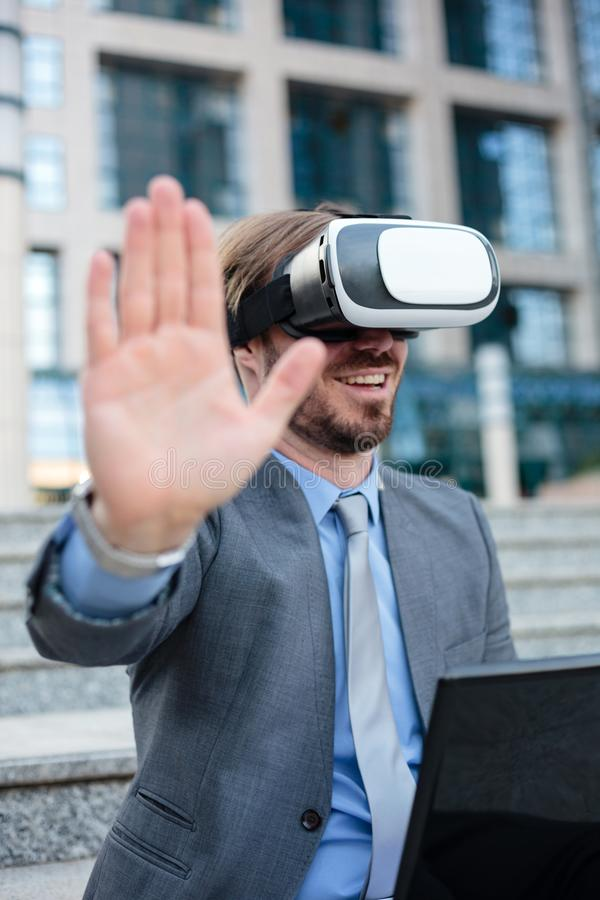 Close up of a young businessman using VR goggles in front of an office building. Selective focus concept, focus on head. Working with modern technologies stock images