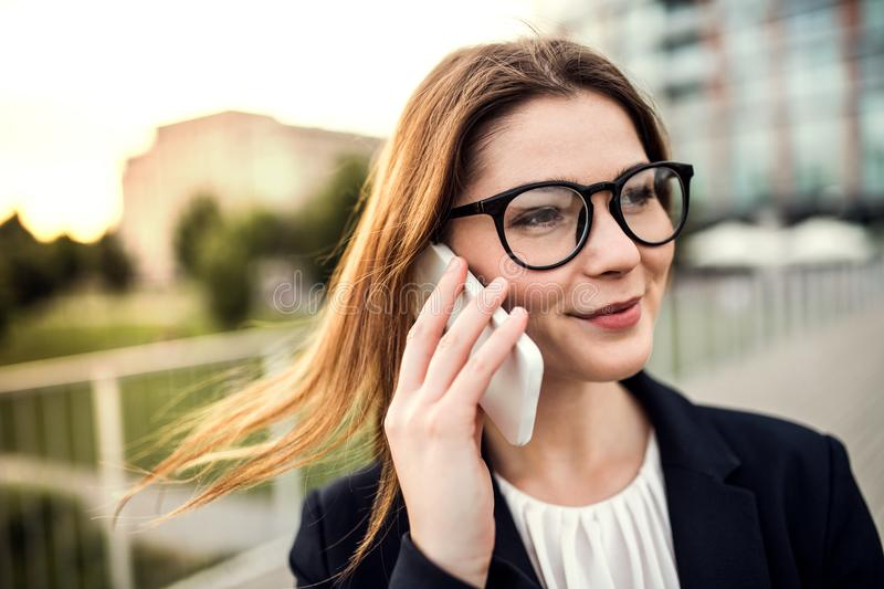 A young businesswoman with smartphone outdoors, making a phone call. stock photography