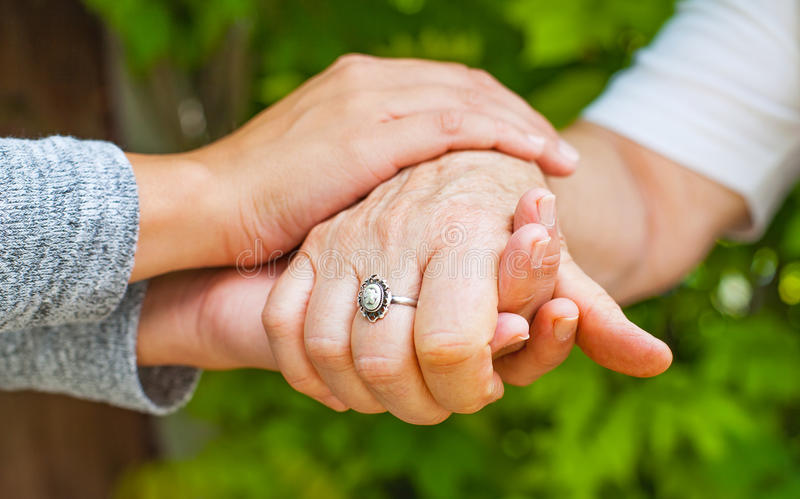 Holding hands, Parkinson disease. Close up young caregiver holding elderly female`s trembling hands, Parkinson disease stock images