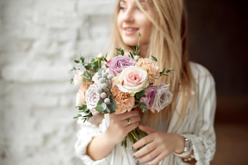 Close-up young caucasian woman holding bouquet of flowers, looks through window with happy smile on face standing in royalty free stock image