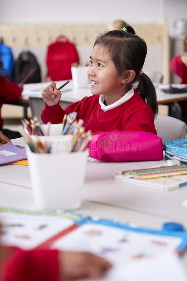 Close up of young Chinese schoolgirl wearing school uniform sitting at a desk in an infant school classroom, selective focus, vert stock photos