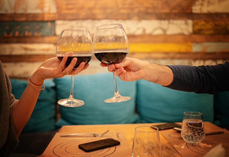 Close up of young couple with glasses of red wine at restaurant. Restaurant, couple, celebration - Close up of young couple with glasses of red wine at stock photo