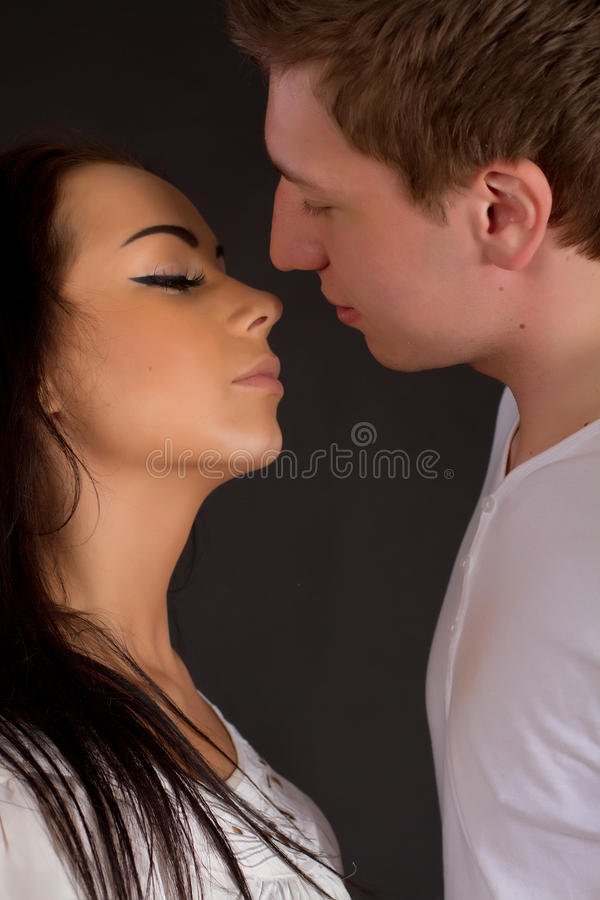 Close up of Young Couple in love kissing. Young Couple in love kissing on black background royalty free stock photo