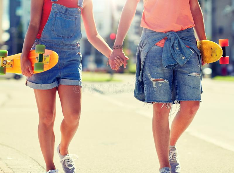 Close up of young couple with skateboards in city. Summer, relations, extreme sport and people concept - close up of happy teenage couple with short modern stock photo