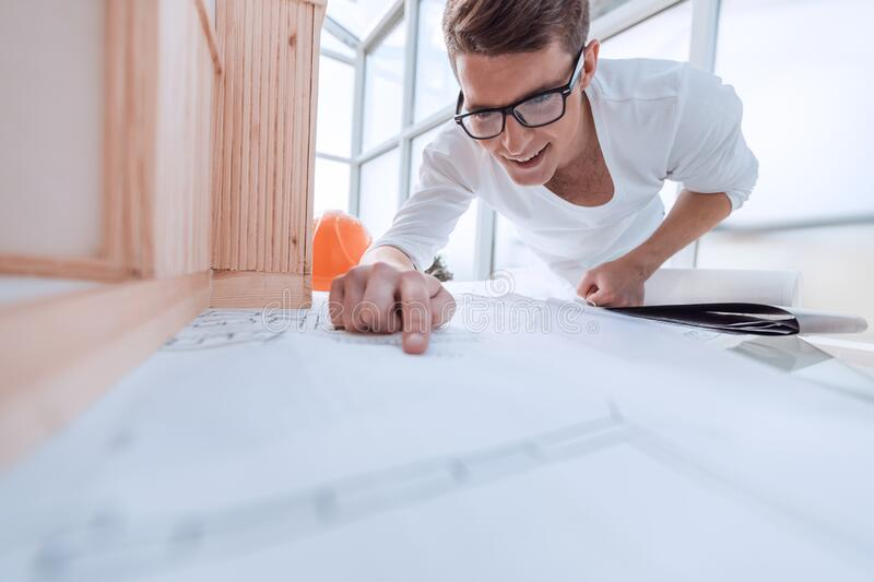 Close up. young designer reading a drawing of a new project. royalty free stock image