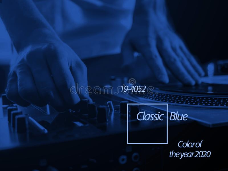 close up young dj playing modern music, color of the 2020 year trend, classic blue tone stock photo
