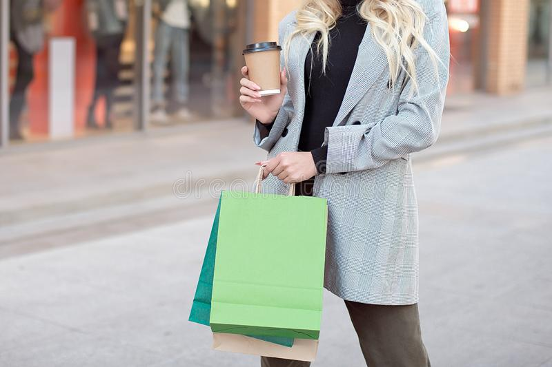 Close-up young fashion woman with shopping bags standing near storefront shop windows on the street outdoors.  stock photos