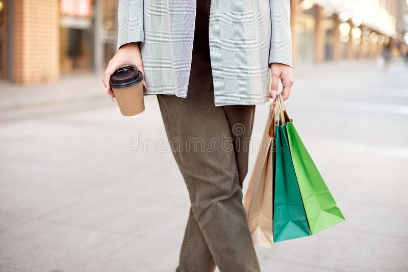 Close-up young fashion woman with shopping bags standing near storefront shop windows on the street outdoors.  stock photo