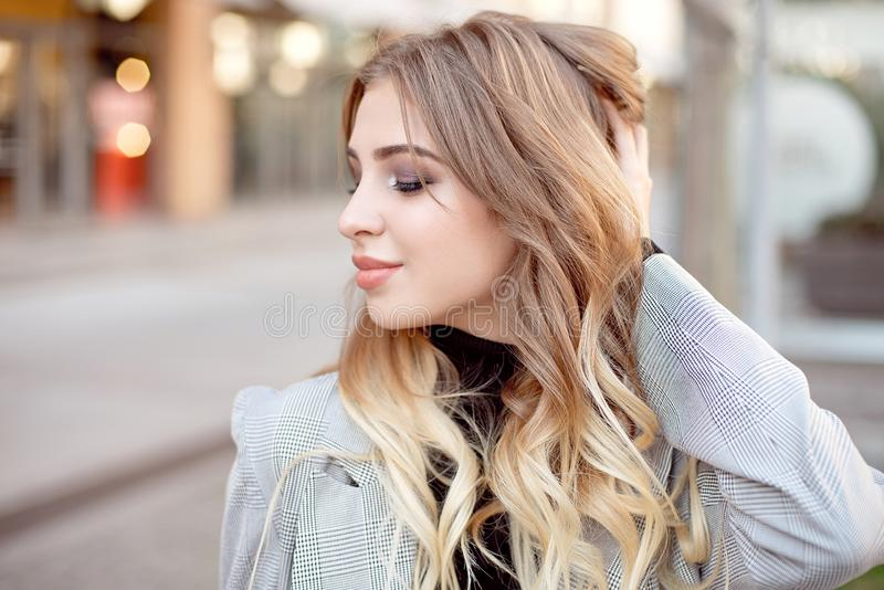Close-up young fashion woman with shopping bags standing near storefront shop windows on the street outdoors.  royalty free stock photo