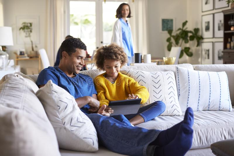 Close up of young father sitting on sofa in the living room with his pre-teen daughter using tablet computer, selective focus, mum stock image