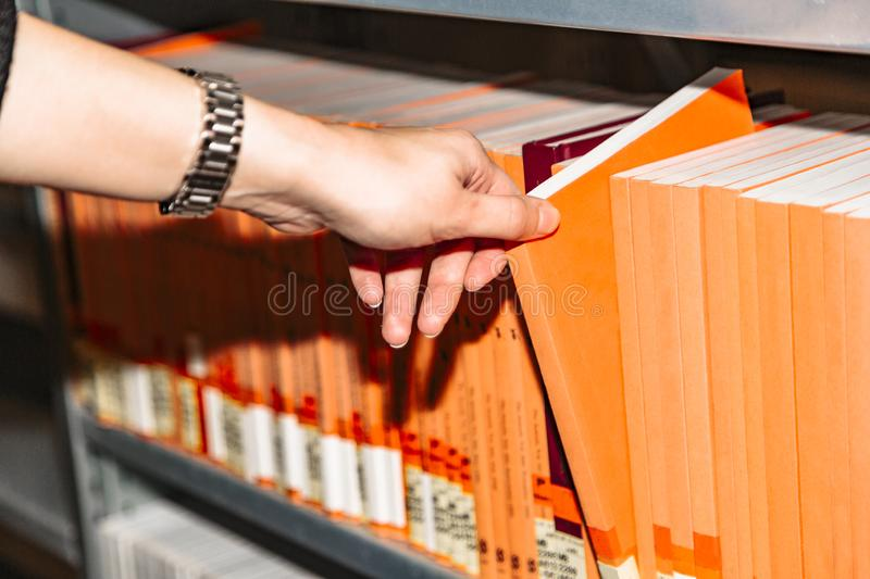 Close up womans hand selecting book from bookshelf stock images