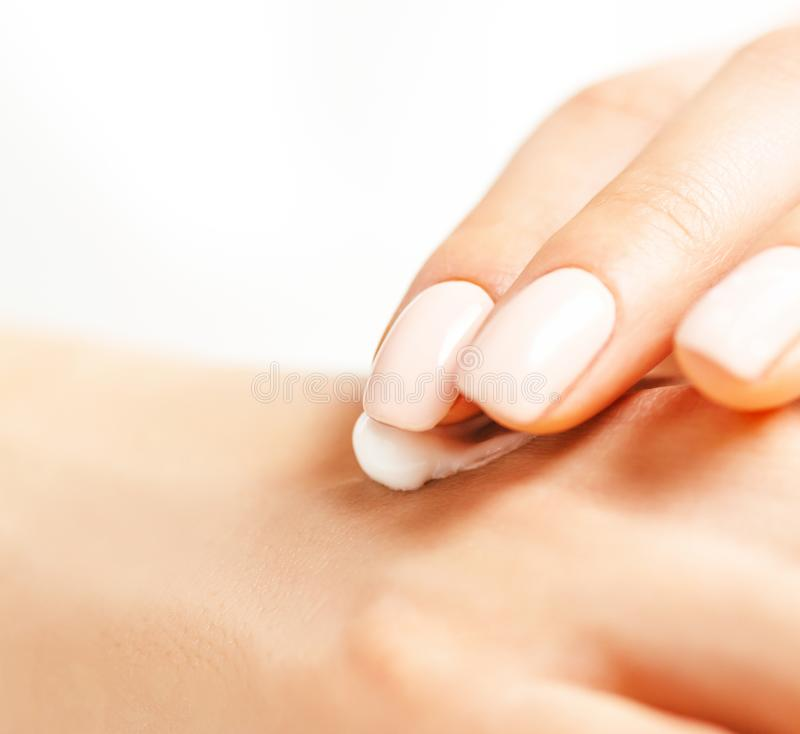 Close-up of female hands applying cream. stock image