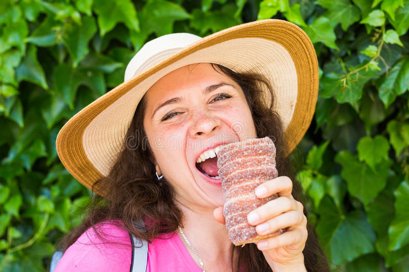 Close-up of young female tourist with traditional czech dessert trdelnik in Prague. Czech Republic. Outdoor.  royalty free stock photos