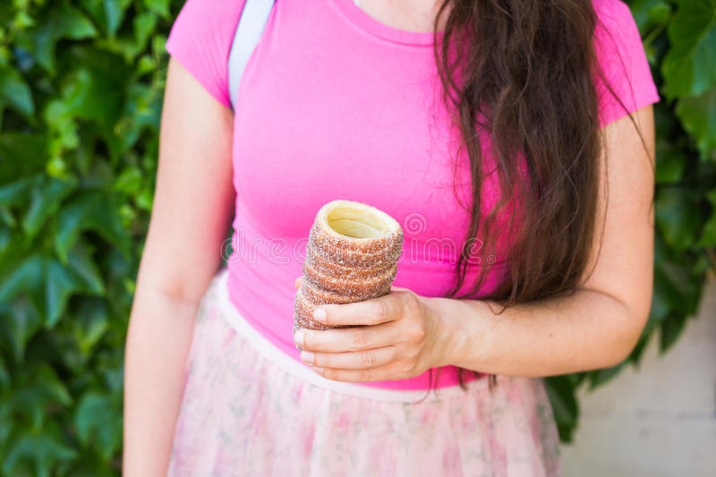 Close-up of young female tourist with traditional czech dessert trdelnik in Prague. Czech Republic. Outdoor.  royalty free stock image