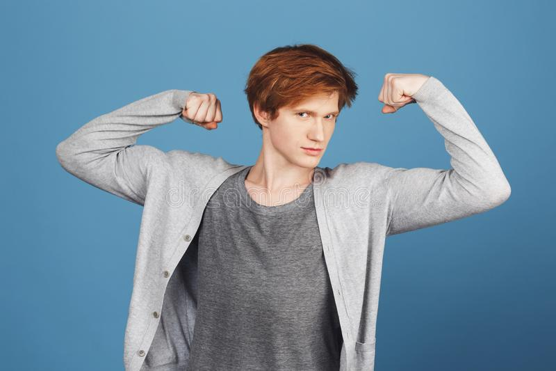 Close up of young funny beautiful red-haired student guy in casual outfit showing his muscles, looking in camera with stock images