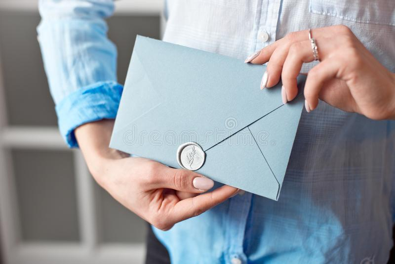 Close-up of a young girl holding a blue rectangular gift envelope with invitations, goods and services card. stock images
