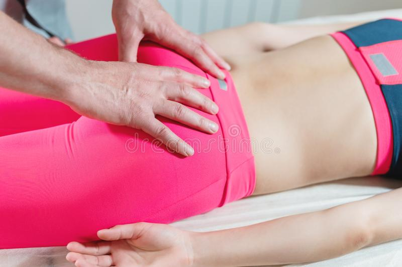 Close-up of a young girl`s spine base editing by a male physiotherapist of visceral massage. The hands of the doctor set royalty free stock photos