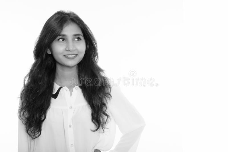 Close up of young happy Persian businesswoman smiling while thinking stock photography