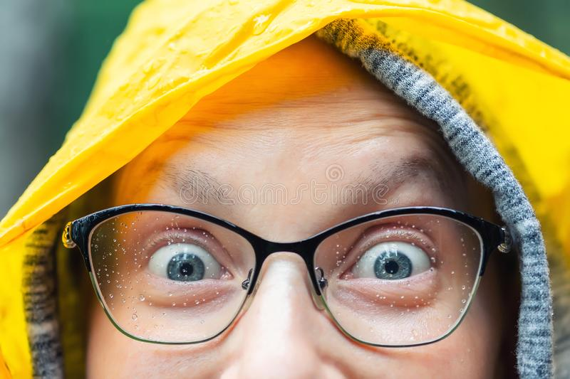 Close-up young happy woman portrait with wide opened amazed eyes wearing glasses with raindrops and bright yellow raincoat hood stock photos
