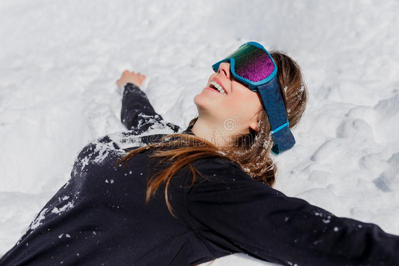 Close up of a young happy woman tourist in ski goggles, posing lying on the snow in winter sunny day. Copy space. stock photos