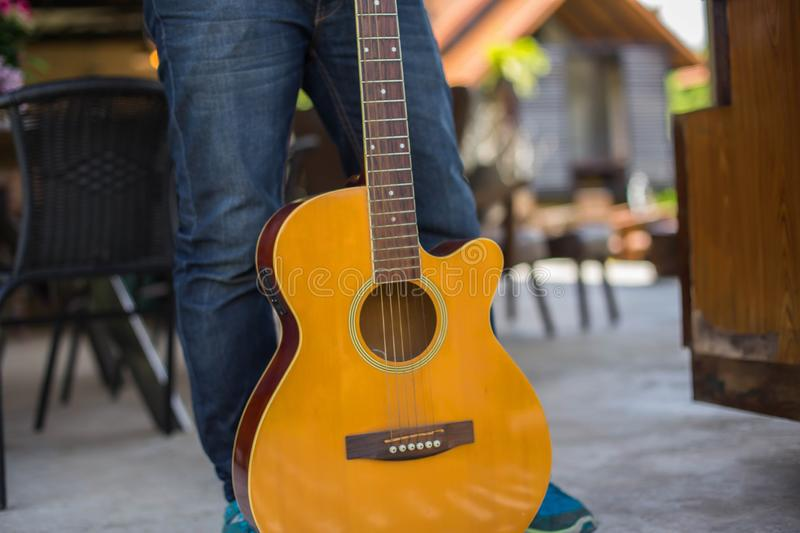 Young hipster man practiced guitar in the park,happy and enjoy playing guitar. royalty free stock images