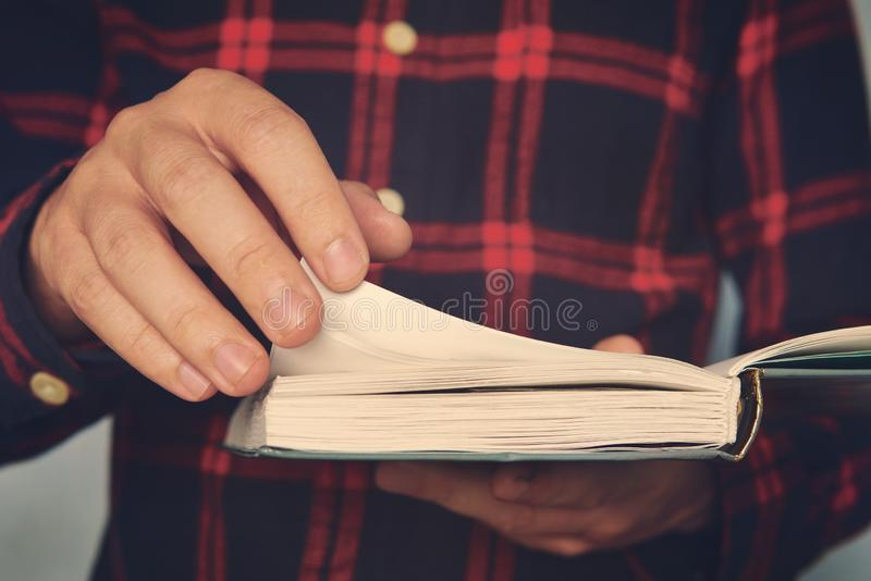 Close up of a young male in a chequered shirt holding the book and turning over the page. Ingusitive man reads the book stock photo