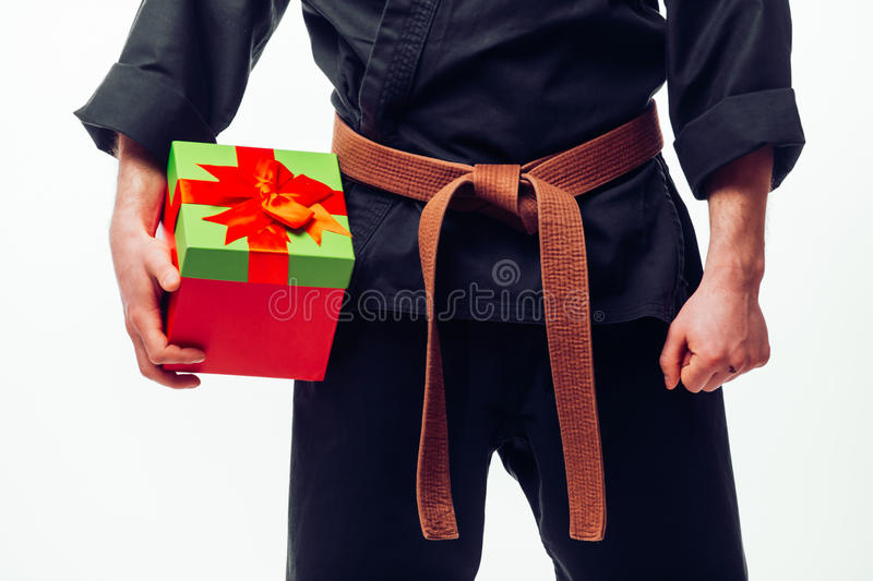 Close up Young male with orange belt karate fighter training with gift box. Young male with orange belt karate fighter training with gift box. Isolated on white royalty free stock photo