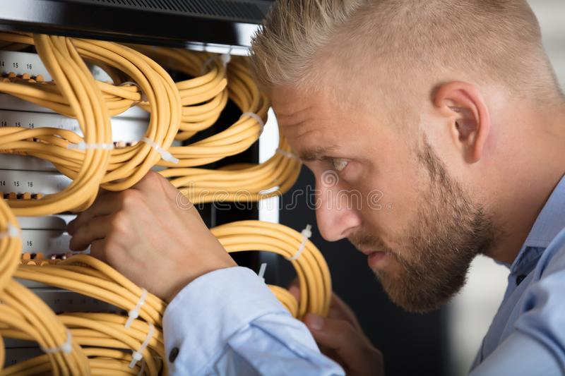 Technician Checking Server`s Wires In Data Center royalty free stock photo