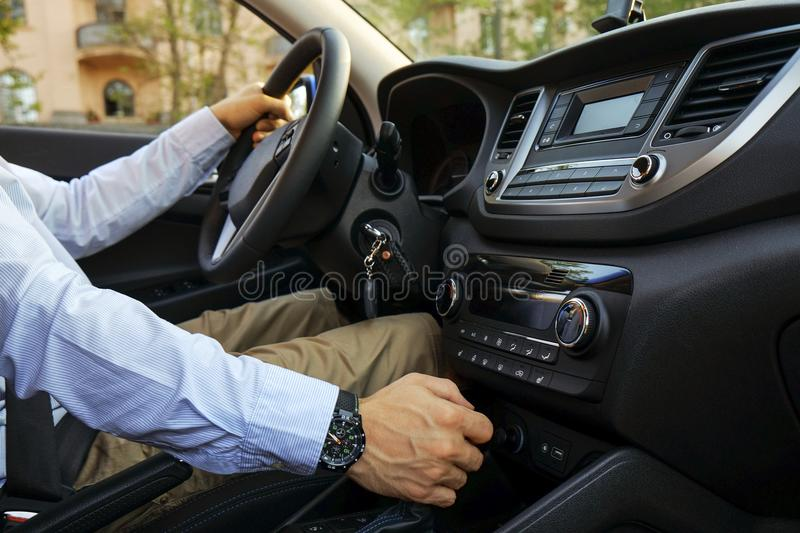 Car interior with male driver sitting behind the wheel, soft sunset light. Luxurious vehicle dashboard and electronics. Close up of young man driving expensive stock photos