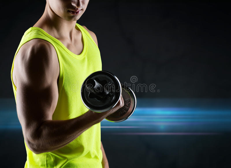 Close up of young man with dumbbell flexing biceps royalty free stock photos
