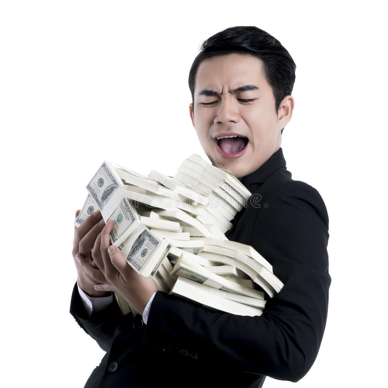Close up the young man excited and holding a large pile of banknotes in arms. stock photography
