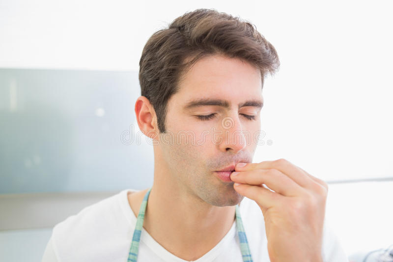 Close up of a young man with eyes closed kissing fingers stock image