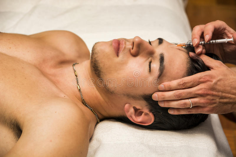 Close-up of young man getting injection of botox. On forehead, laying down with eyes closed royalty free stock photography