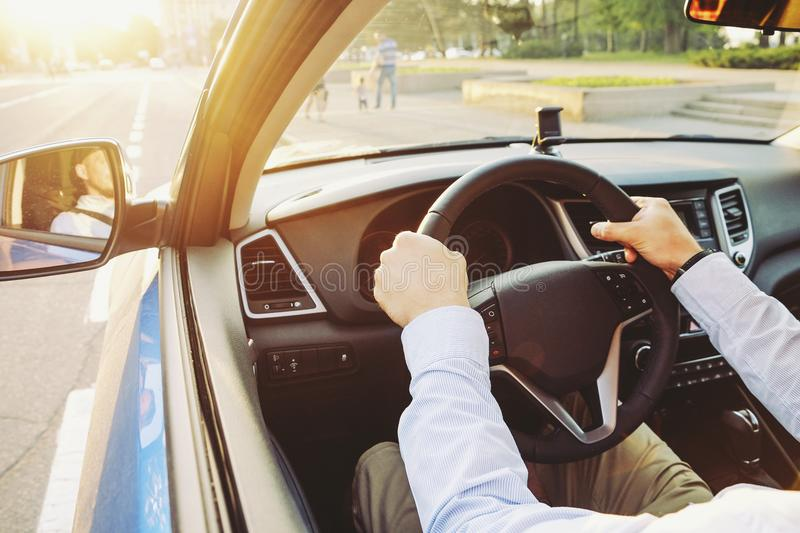 Car interior with male driver sitting behind the wheel, soft sunset light. Luxurious vehicle dashboard and electronics. Close up of young man hands holding royalty free stock photo