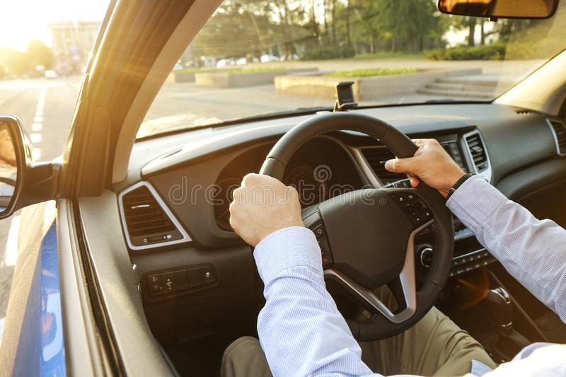 Car interior with male driver sitting behind the wheel, soft sunset light. Luxurious vehicle dashboard and electronics. Close up of young man hands holding royalty free stock photos