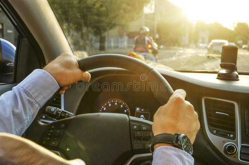 Car interior with male driver sitting behind the wheel, soft sunset light. Luxurious vehicle dashboard and electronics. Close up of young man hands holding stock photography