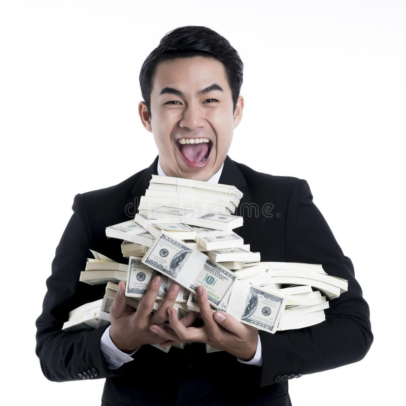 Close up the young man happy and carrying a large pile of banknotes in arms. stock image