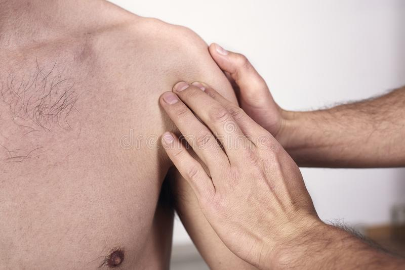 Close-up of a young man having chiropractic shoulder adjustment. Physiotherapy, sports injury rehabilitation. Osteopathy, stock photos