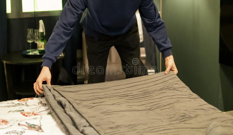Close up young man making a bed at home bedroom v stock photography