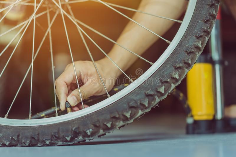 Close-up of a young man prepare to pumping the old bicycle wheel stock photography